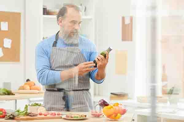 bearded senior man cooking 3QALG6G